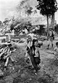 With a few salvaged belongings in the background, a Vietnamese woman carries a baby and pulls her daughter away as their home erupts in flames in July 1963. The woman and children may have been left behind so as not to slow other villagers escaping into the jungle. (AP Photo/Horst Faas) Source:  http://killanythingthatmoves.tumblr.com/