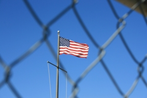 American flag behind a chain link fence. (Image: via Shutterstock)