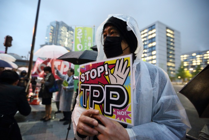 A man holds a placard as he takes part in a protest against Trans-Pacific Partnership (TPP) trade talks outside the prime minister's official residence in Tokyo, Japan in April 2014. Photo credit: Bloomberg
